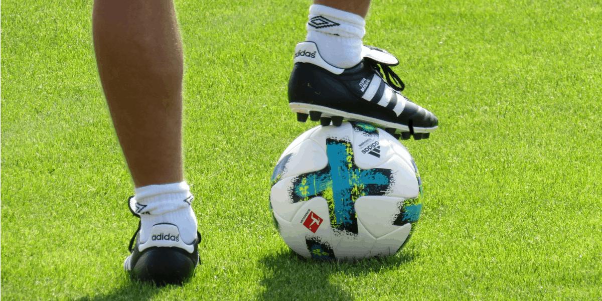 pessoa em campo usando uma chuteira de society com uma bola de futebol
