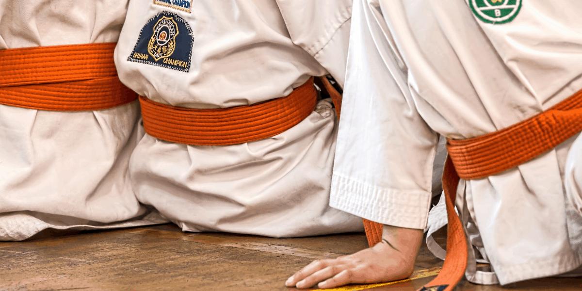 3 pessoas usando kimonos de karatê sentadas no chão